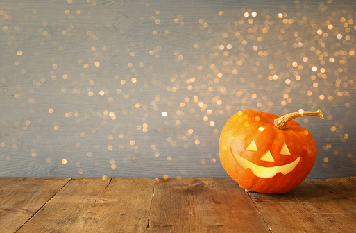 Halloween holiday concept. Cute pumpkin on wooden table and glitter lights overlay