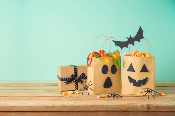 Halloween holiday concept with party gift paper bags decor and candy on wooden table stock photo