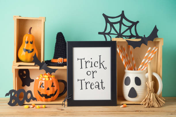 Halloween holiday concept with photo frame, jack o lantern cup, candy corn and decorations on wooden table stock photo