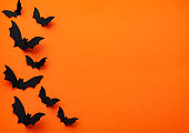 halloween  concept - black paper bats flying over orange background