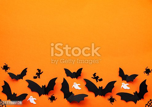 holidays  concept - halloween paper decorations and sweets with blank copy space over orange background
