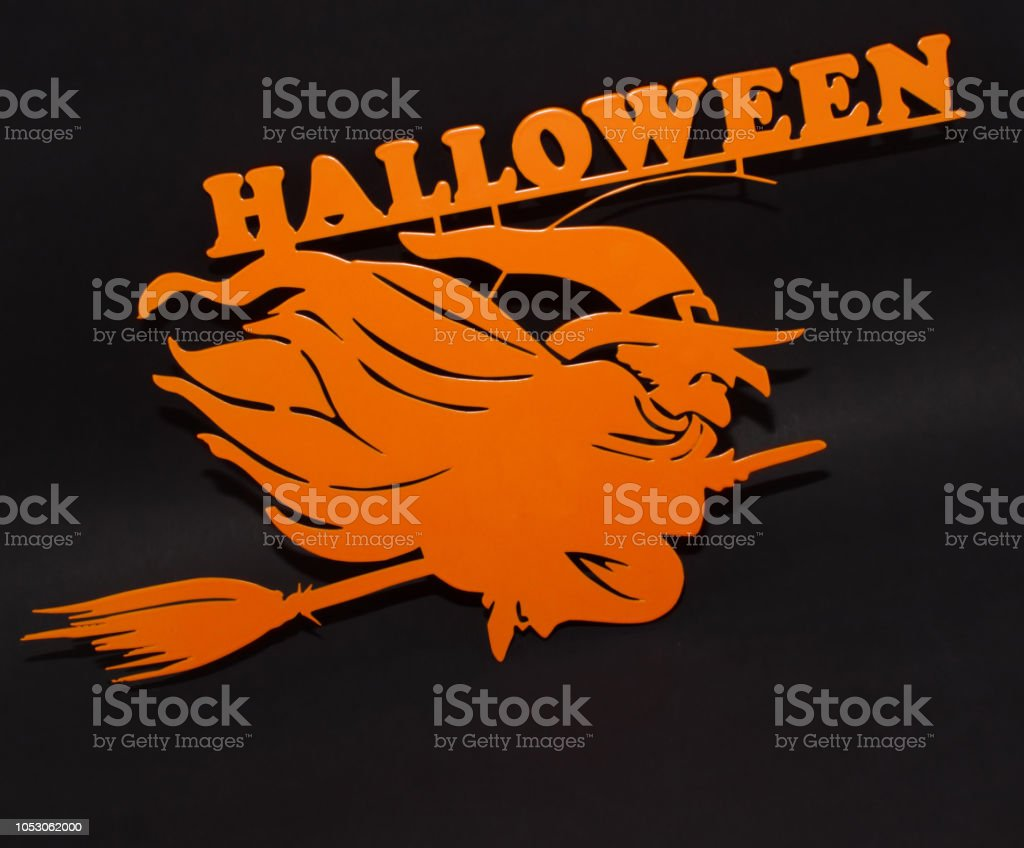 Halloween holiday metal top view image of orange witch over black background stock photo