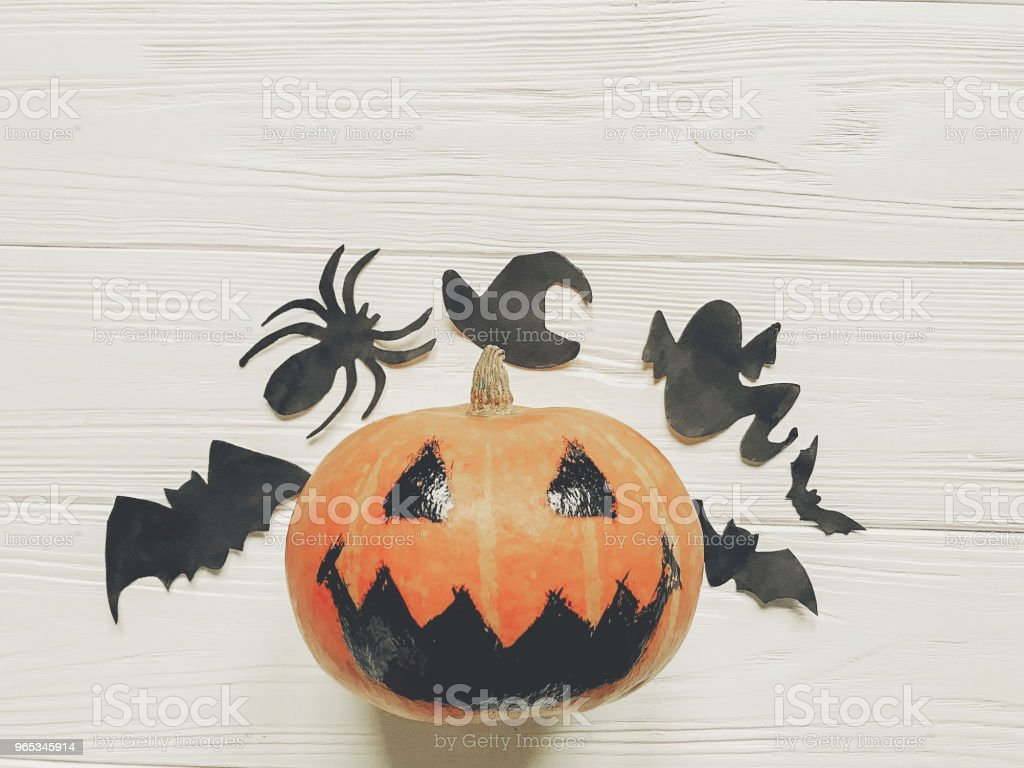 halloween. jack lantern pumpkin with witch ghost bats and spider black decorations on white wooden background top view. seasonal greetings. happy halloween concept, space text royalty-free stock photo