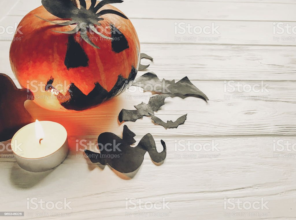 halloween. jack lantern pumpkin with witch ghost bats and spider black decorations on white wooden background. simple cutouts for autumn holiday celebration. seasonal greetings royalty-free stock photo