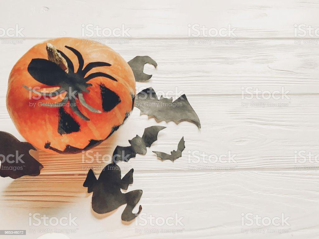萬聖節。傑克燈籠南瓜與女巫幽靈蝙蝠和蜘蛛黑色裝飾品在白色的木質背景。秋季節日慶典的簡易切口。季節性問候語 - 免版稅傳統圖庫照片