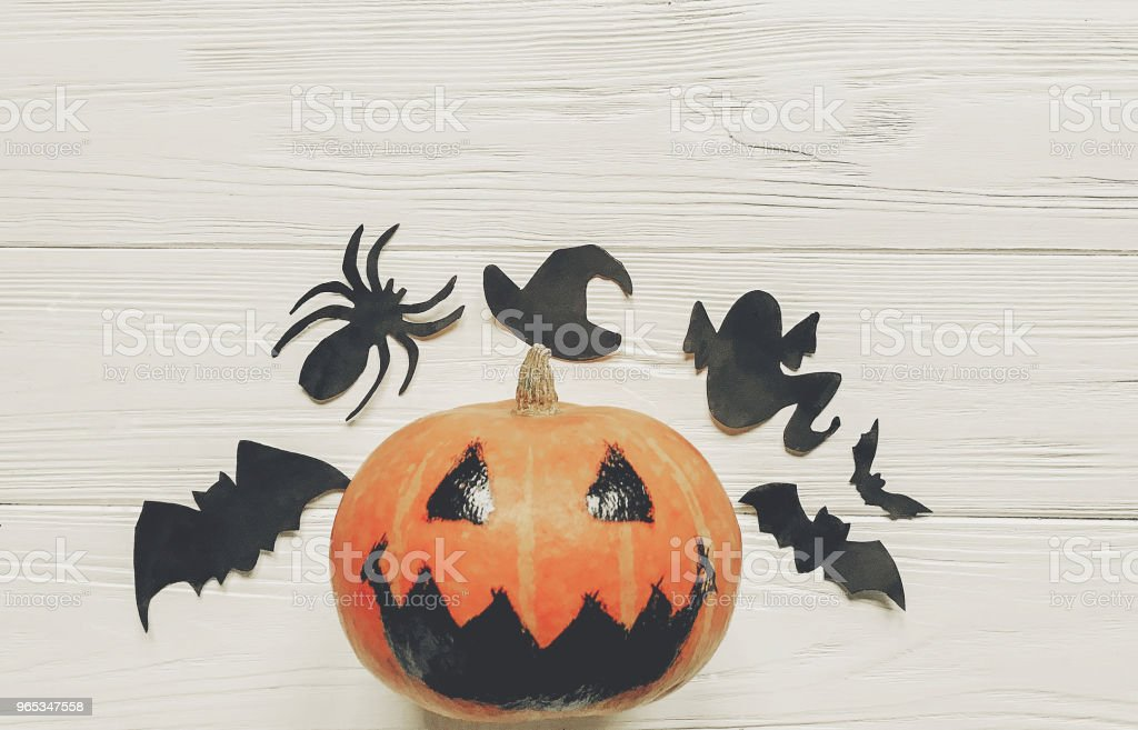 halloween. jack lantern pumpkin with witch ghost bats and spider black decorations on white wooden background. simple cutouts for autumn holiday celebration. space for text royalty-free stock photo