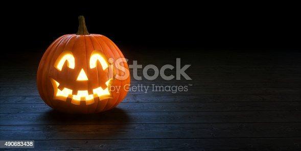 A solitary Jack O' lantern sitting on a dark wooden floor under soft spotlight illumination.