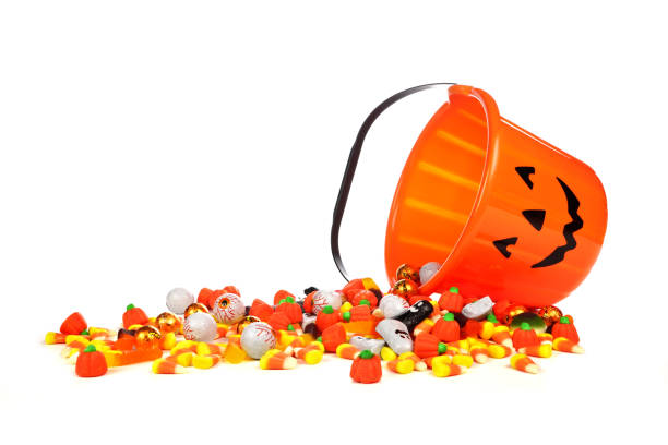 halloween jack o lantern candy collector with spilling candy over white - halloween candy стоковые фото и изображения