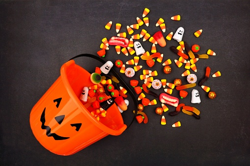 Halloween Jack o Lantern pail with spilling candy, above view on a dark background