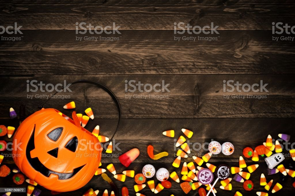 Halloween Jack o Lantern pail with bottom border of spilling candy over dark wood stock photo
