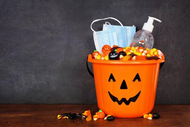 cubo de halloween jack o lantern con suministros de prevención de caramelos y coronavirus sobre un fondo oscuro - halloween covid fotografías e imágenes de stock