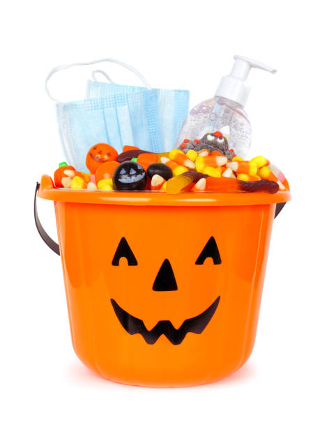 Halloween Jack o Lantern pail with candy and COVID 19 prevention supplies isolated on white stock photo