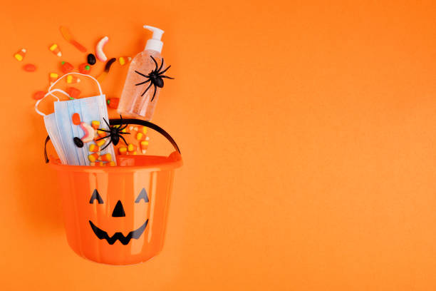 cubo de halloween jack o lantern con suministros de prevención de caramelos y coronavirus derramados sobre un fondo naranja - halloween covid fotografías e imágenes de stock