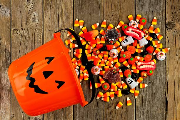 Halloween Jack o Lantern pail with spilling candy over wood - Photo