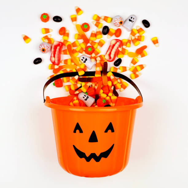 halloween jack o lantern pail with spilling candy, top view on a white background - halloween candy стоковые фото и изображения