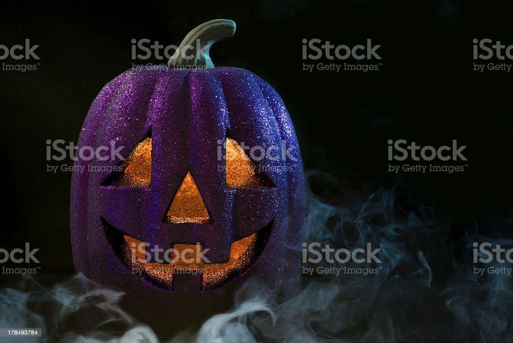 Halloween Jack o' lantern Purple Halloween Jack o' lantern with fog Black Background Stock Photo