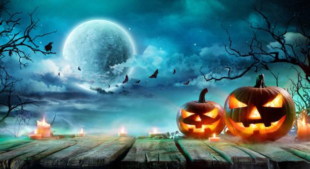 cadılar bayramı - jack o'fener ve mumlar misty gece masada - halloween background stok fotoğraflar ve resimler