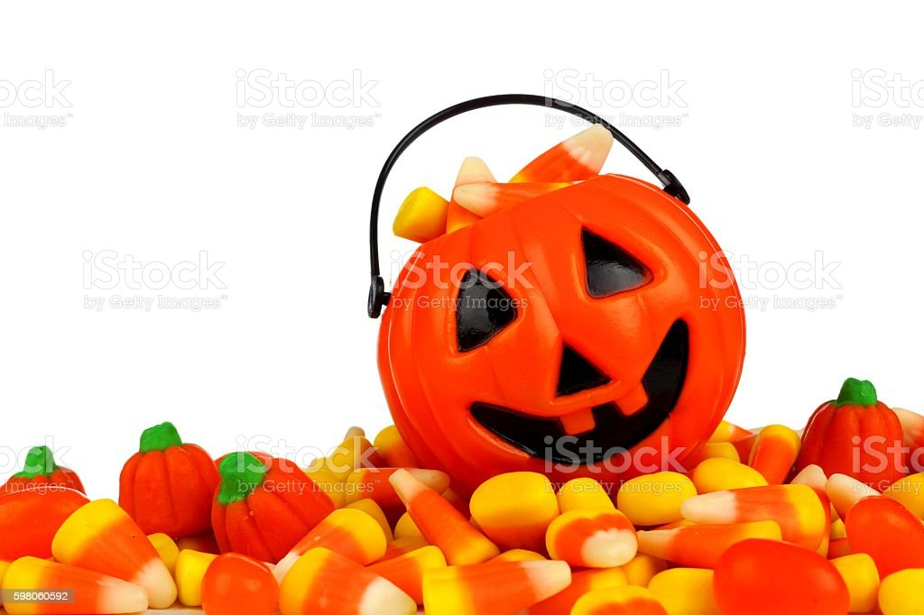 Halloween Jack-o-Lantern pail on a pile of candy over white stock photo