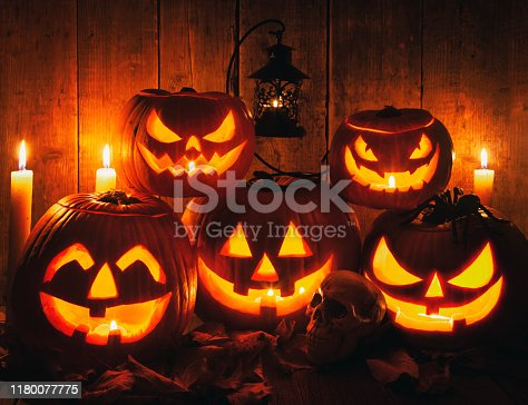 Halloween Jack-o-Lantern Pumpkins on rustic wooden background