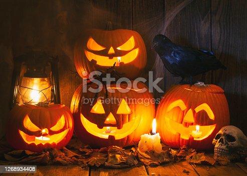 Halloween Jack-o-Lantern Pumpkins on rustic wooden background
