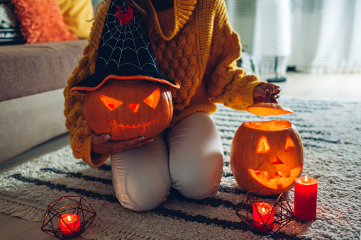 Halloween jack-o-lantern pumpkins. Woman holds hand-made carved pumpkin and opens another one. Home decarated with traditional symbols.