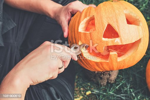 A close up of man's hand who cuts with knife a pumpkin as he prepares a jack-o-lantern. Halloween. Decoration for party. Toned photo.
