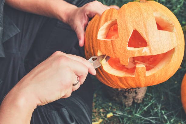 Halloween . Jack-o-Lantern. scary pumpkin with a smile A close up of man's hand who cuts with knife a pumpkin as he prepares a jack-o-lantern. Halloween. Decoration for party. Toned photo. carving craft product stock pictures, royalty-free photos & images