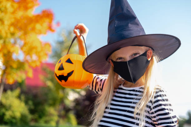 Halloween kids mask. Portrait blonde girl in witch costume with pumpkin bucket. Child wearing black face masks outdoors protecting from COVID-19 Halloween kids mask. Portrait blonde girl in witch costume with pumpkin bucket. Child wearing black face masks outdoors protecting from COVID-19. halloween covid stock pictures, royalty-free photos & images