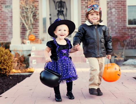 A young brother and sister dress up for Halloween.