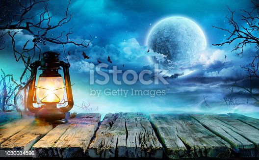 Oil Lamp On Wooden Table In Spooky Night