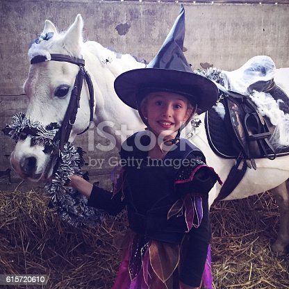 Little girl dressed up for halloween with a pony