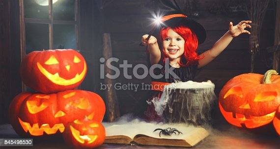 istock Halloween. little witch child cooking potion   with pumpkin and spell book 845498530