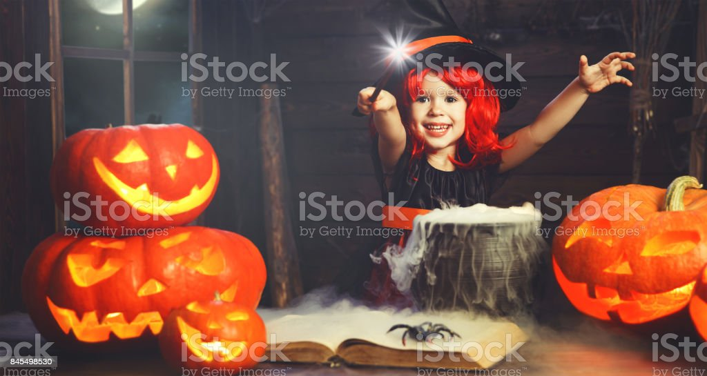 Halloween. little witch child cooking potion   with pumpkin and spell book stock photo