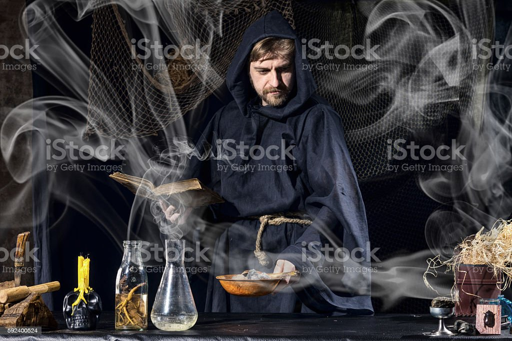 Halloween magician is preparing for  magical ritual in ancient table stock photo