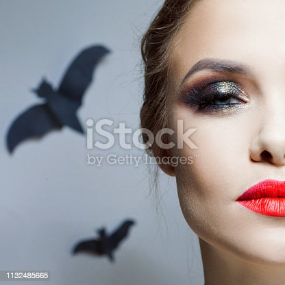 Halloween makeup, bright and stylish girl with red lips and Smokey eyes makeup. bats on background