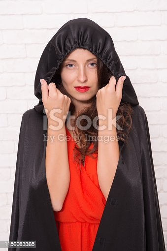 512061362istockphoto Halloween masquerade. Halloween party. Damn pretty woman devil. Death in black cloak symbol. Vampire in cloak sexy devil girl. Woman tempting vampire demon. Girl covered with cloak. Devil concept 1156083365