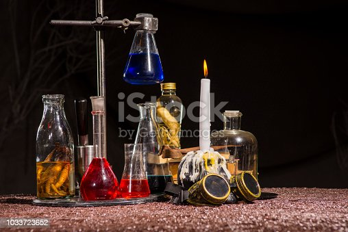 Halloween. Medieval alchemist's table. Flasks with multi-colored liquids. Scientist-encyclopedist room interior. Old reconstruction