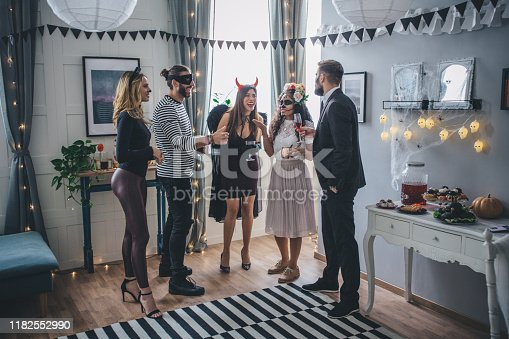 Group of Young people at home celebrating Halloween in costumes, they enjoy in good atmosphere