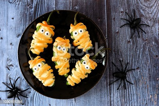 Plate of Halloween mummy jalapeno poppers, top view with a dark wood background with spiders