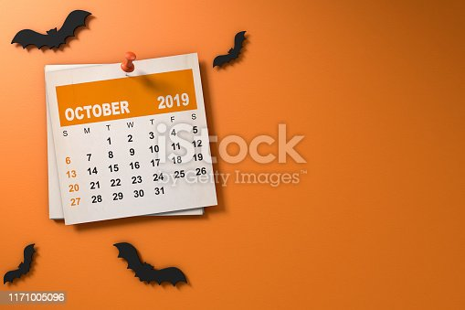 Halloween October 2019 calendar on orange background with paper craft bats and copy space.
