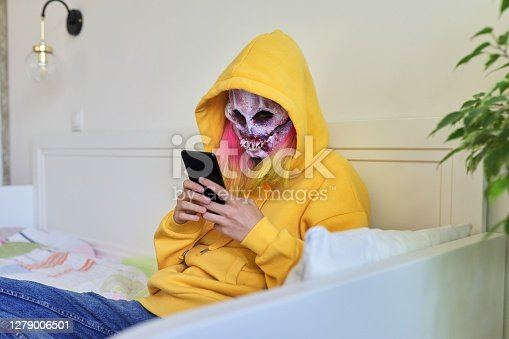 Halloween party at home, isolation and quarantine, teenage girl in scary hoodie mask with smartphone making video call, online halloween celebration