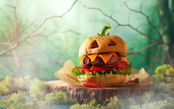 Halloween-Party-Burger in Form von gruseligen Kürbis auf natürlichem Holzbrett. – Foto