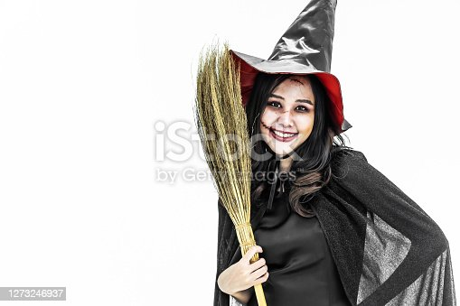 Halloween party Girl wearing witch costume with a hat, Celebrating. Beauty asian woman with long hair standing and smiling holding  broomstick isolated on white background.