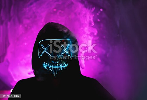 Halloween party incognito in a glowing mask portrait . Purple shades skoke background