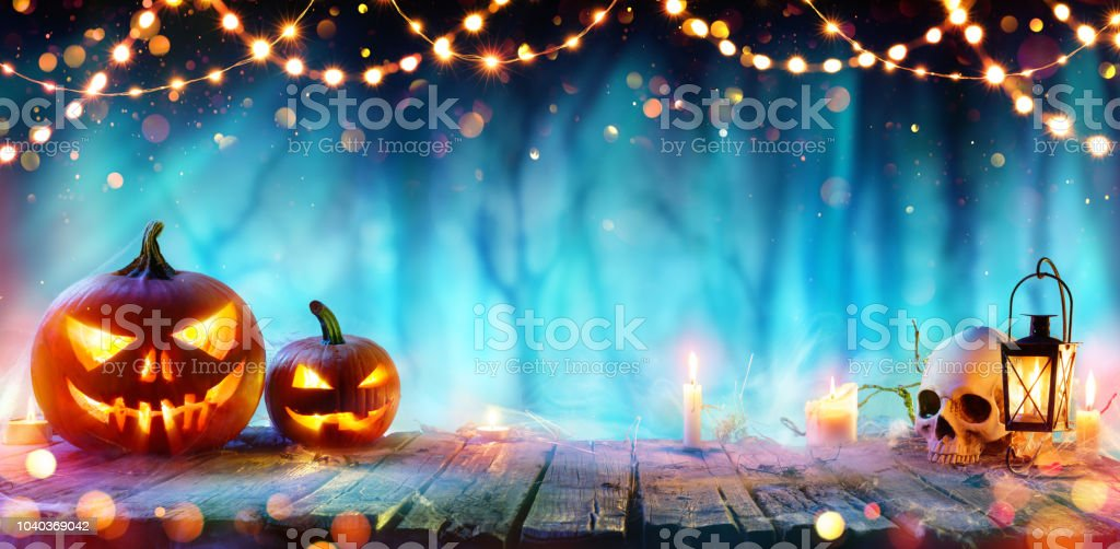 Fiesta de Halloween - gato o linternas y luces de la secuencia sobre mesa en bosque de Misty - Foto de stock de Azul libre de derechos