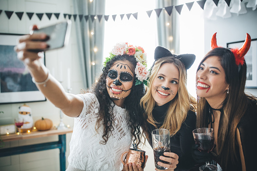 Group of Young people at home celebrating Halloween in costumes, they taking selfie