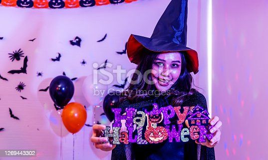Halloween party with a girl holding a Happy Halloween sign in hand
