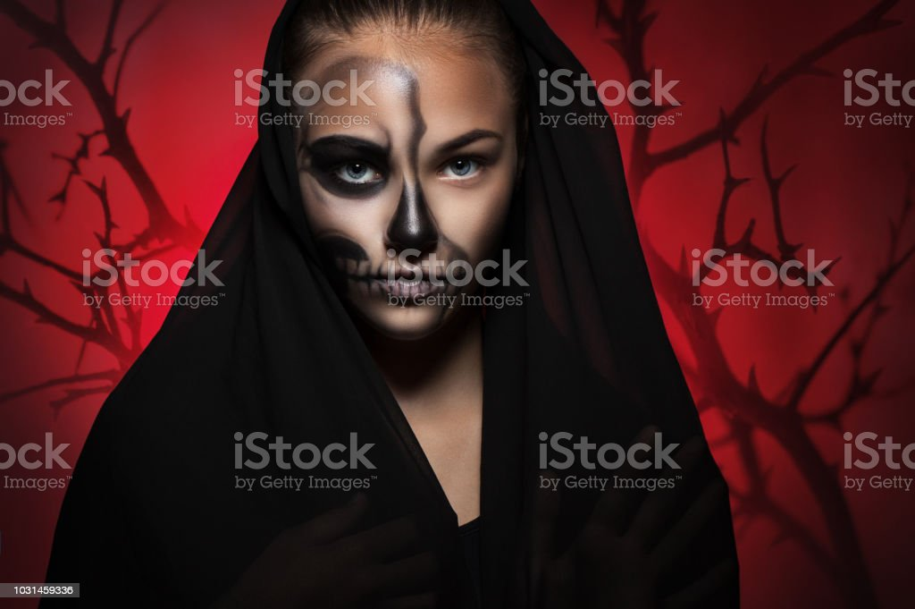 f3a0bec4a4d Halloween portrait of a young beautiful girl in a black hood. skeleton  make-up half face. - Stock image .