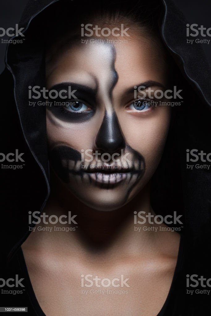 a8deccd6cab Halloween portrait of a young beautiful girl in a black hood. skeleton  make-up half face - Stock image .