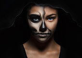 istock Halloween portrait of a young beautiful girl in a black hood. skeleton make-up half face 1031459586